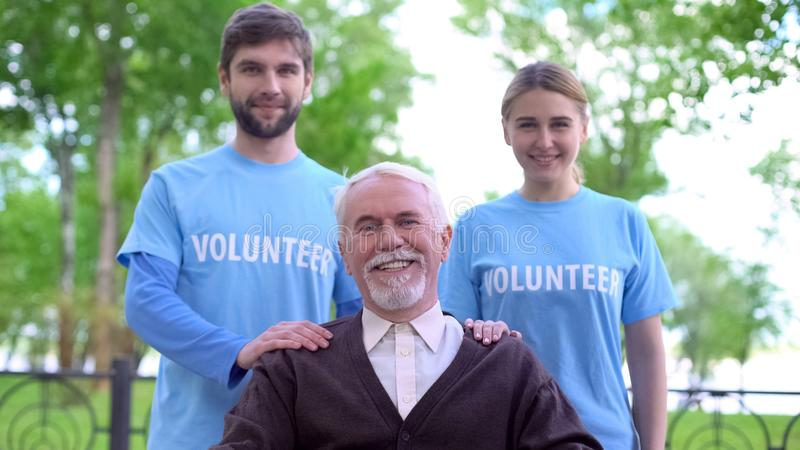 Happy senior man and two volunteers smiling at camera, elderly people support. Happy senior men and two volunteers smiling at camera, elderly people support royalty free stock photography