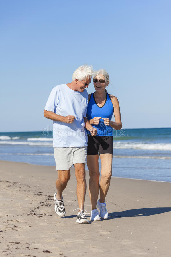 Healthy Senior Couple Running Jogging on Beach royalty free stock photos