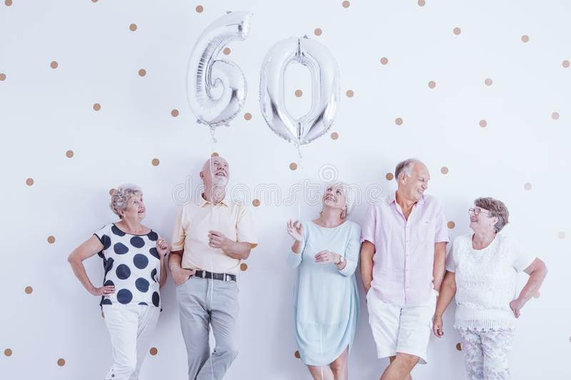 Happy senior man and woman holding silver balloons. stock photo
