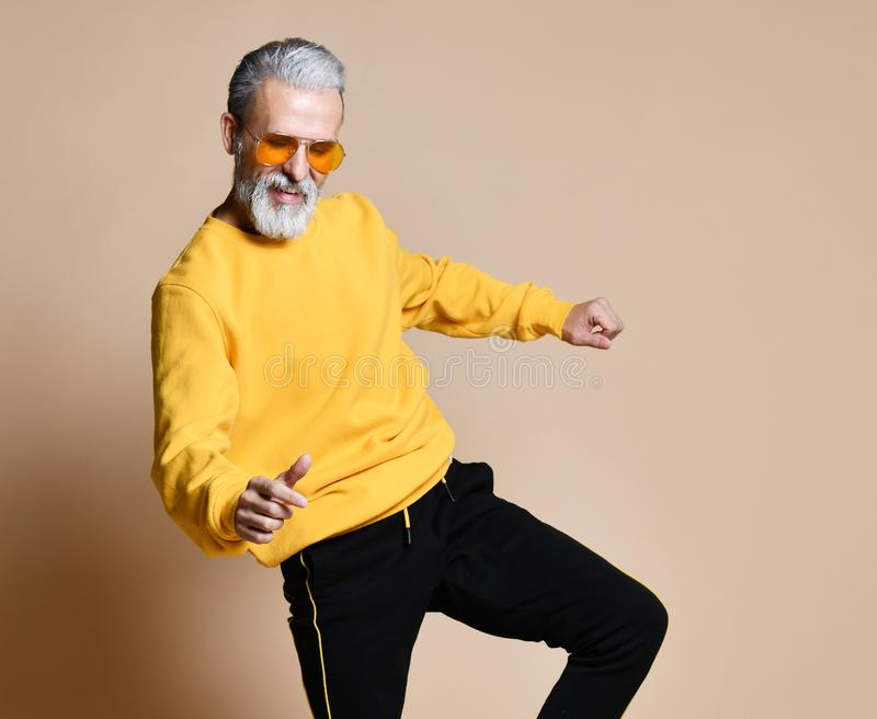 Happy senior millionaire man dancing in yellow sunglasses stylish fashionable men senior royalty free stock photo