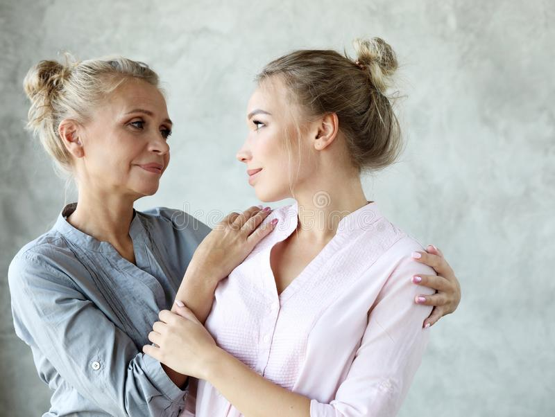 Happy senior mother embracing adult daughter laughing together, smiling excited aged older lady hugging young woman stock photos