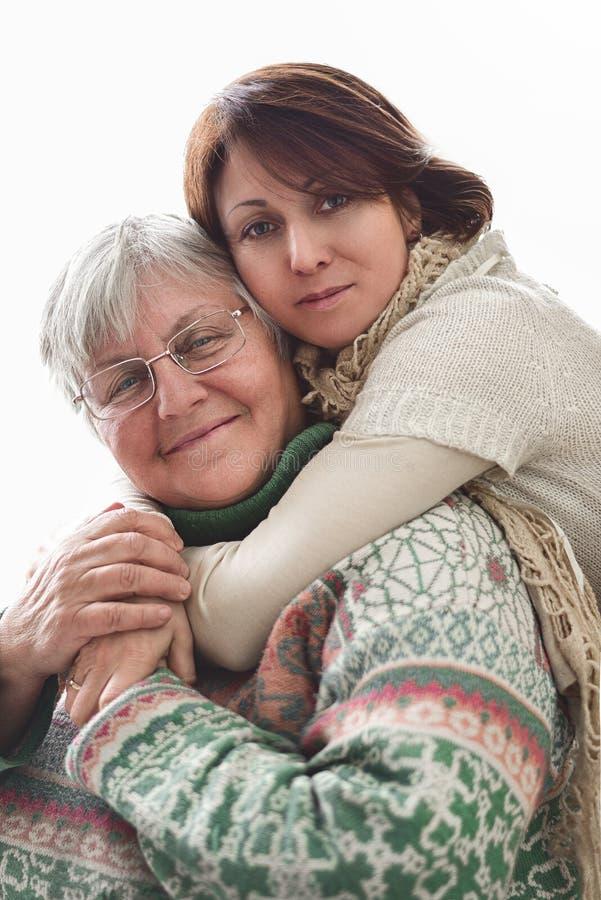 Happy Senior Mutter und erwachsene Tochter schließen Portrait auf weißem Hintergrund stockfotos
