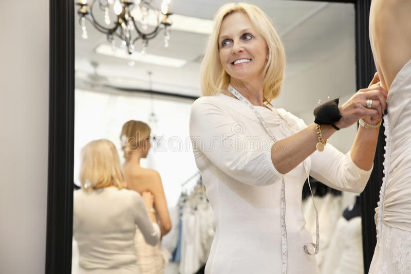 Happy senior owner with pincushion in wrist helping bride getting dressed stock image