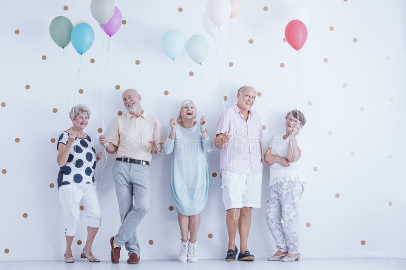 Happy senior people with colorful balloons celebrating friend`s birthday. Concept stock photo