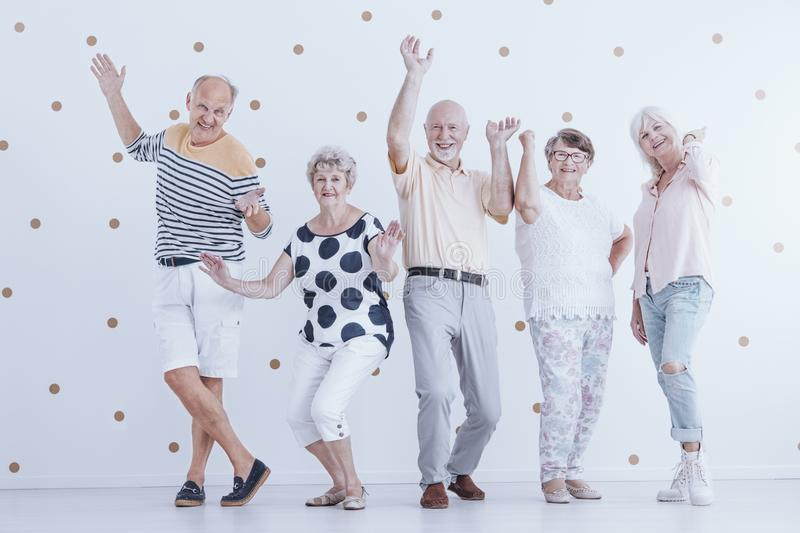 Happy senior people dancing against white background with gold d stock photography