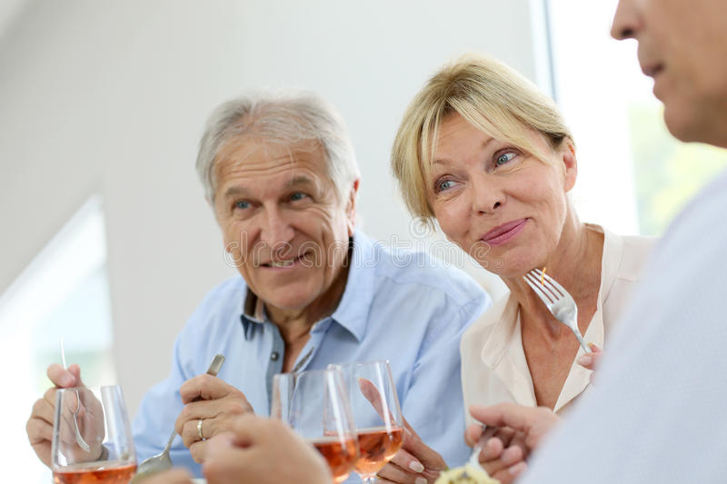 Happy senior people at dinner stock photography
