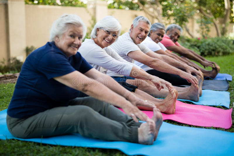 Happy senior people doing stretching exercises at park royalty free stock photo
