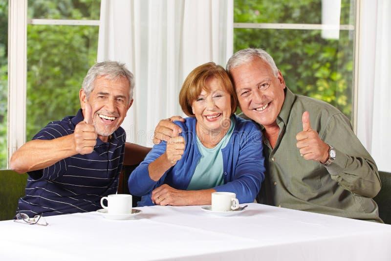 Happy senior people holding thumbs stock photo