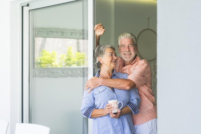Happy senior people at home in retired lifestyle - active seniors smile and hug with love and relationship - indoor leisure. Activity for mature men and woman royalty free stock image