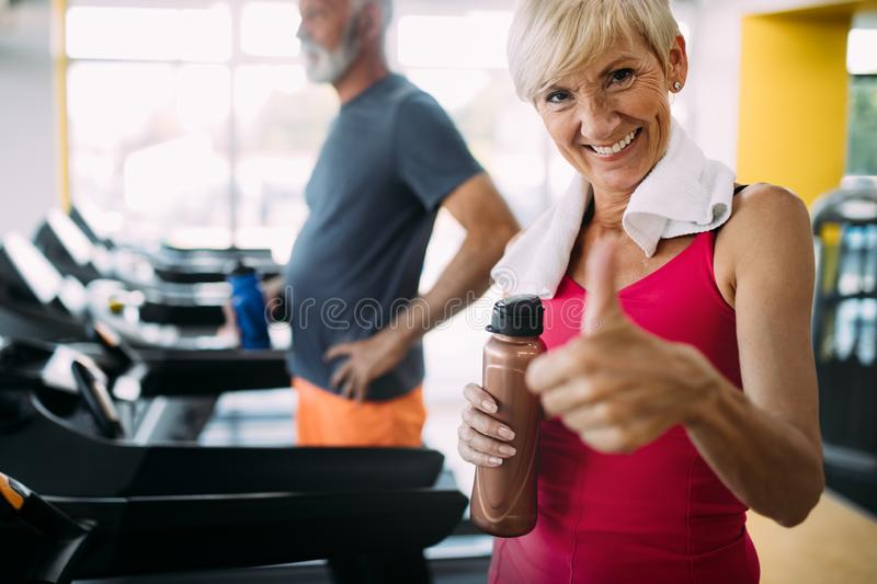 Happy senior people running together on treadmills in gym. royalty free stock images