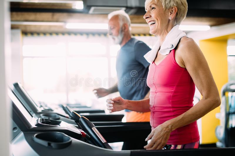Happy senior people running together on treadmills in gym. stock image