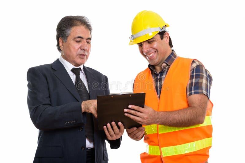 Happy senior Persian businessman and young Persian man construct royalty free stock image