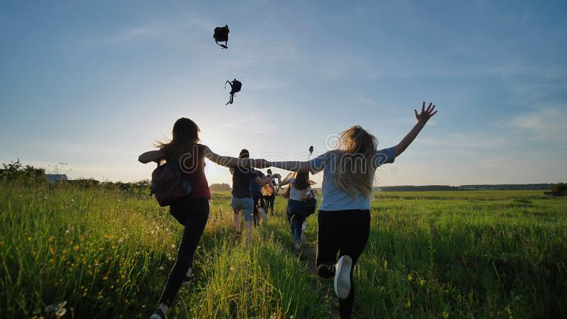 Happy senior pupils flee and toss their portfolios against the sunset. Happy ending school days. Slow motion. Happy senior pupils flee and toss their portfolios stock image
