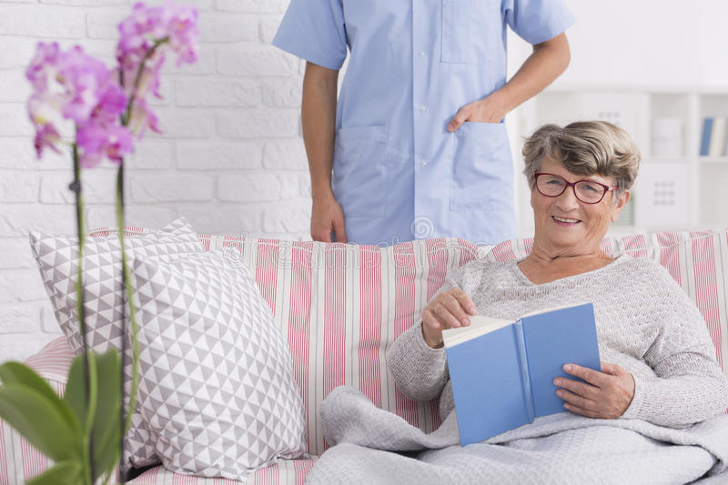 Happy senior reading in retirement home. Happy senior women reading a book in retirement home with carer royalty free stock images