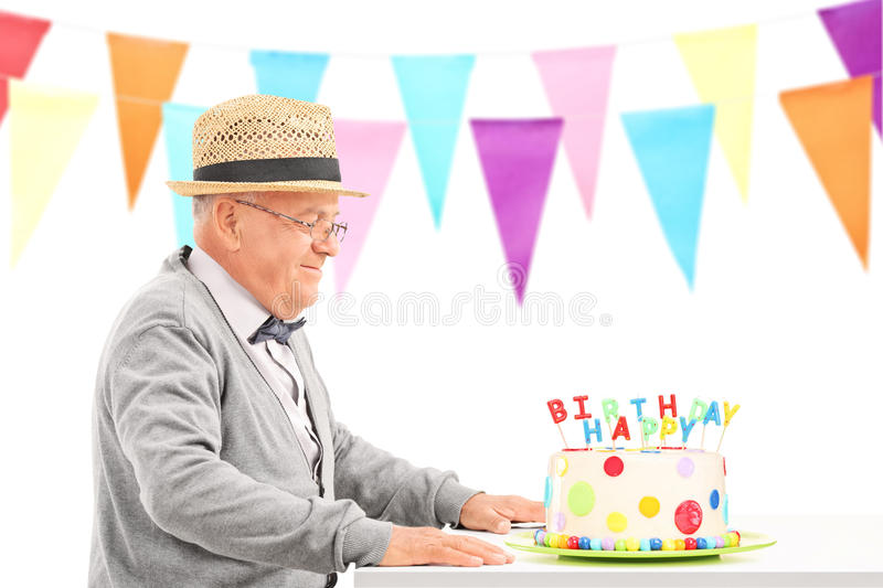 Happy senior sitting at a table with birthday cake. Isolated on white background royalty free stock image