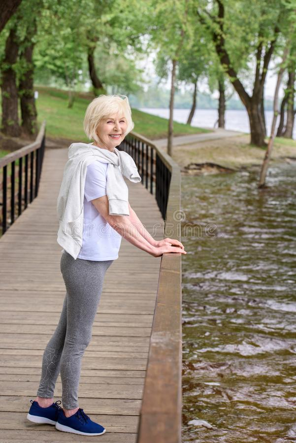 happy senior sportswoman standing on wooden path near railings stock photography