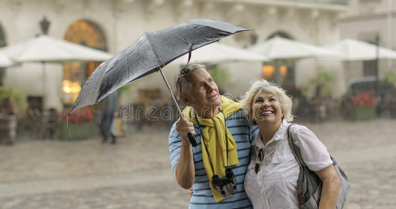 Happy senior tourists stand downtown and enjoy the rainy weather in Lviv stock photo