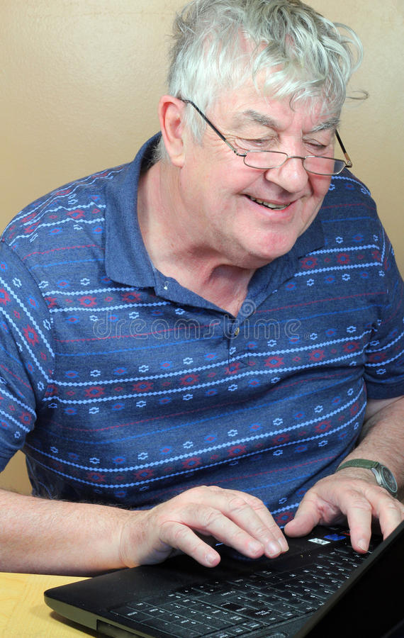 Happy senior using his laptop. stock image