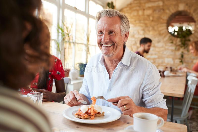 Happy senior white man eating brunch with friends at a cafe stock photo