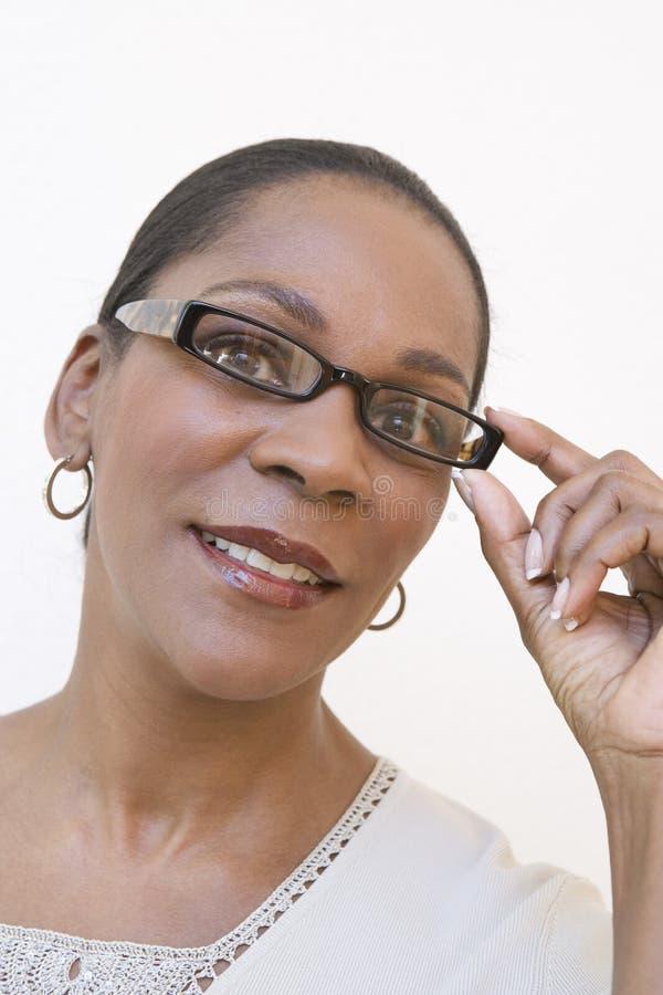 Happy Senior Woman Adjusting Glasses royalty free stock image