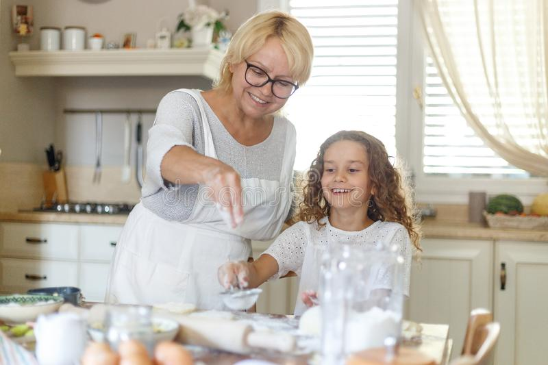 Happy senior woman with adorable granddaughter cooking together on kitchen, they feel good together. Horizontal view. royalty free stock images