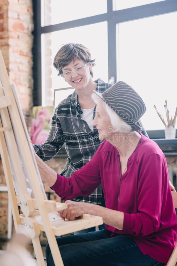 Happy Senior Woman in Art Class. Side view portrait of modern senior women painting sitting at easel in art studio studying art with smiling female teacher stock photos