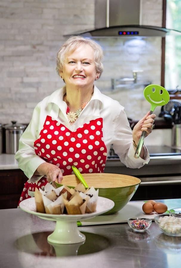 Free Happy Senior Woman Baking In A Bright Modern Kitchen Stock Image - 189599131