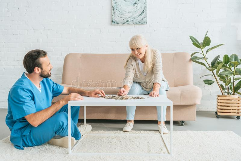 Happy senior woman and caregiver playing with jigsaw puzzle. Pieces royalty free stock photography