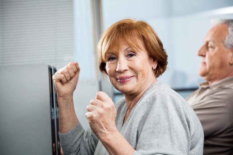 Happy Senior Woman Cheering In Computer Class. Portrait of happy senior women cheering with classmate in background at computer class stock image
