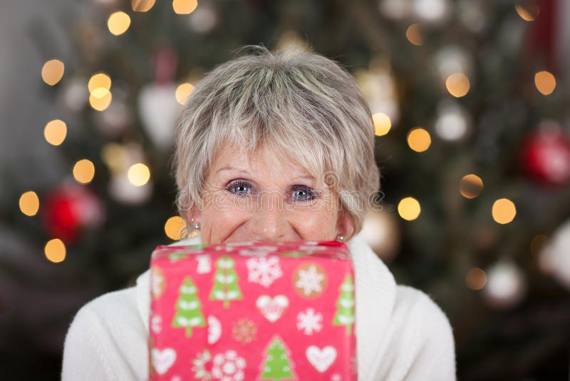 Happy senior woman with a Christmas gift. In front of the lower half of her face looking at the camera with laughing eyes, Christmas tree backdrop with royalty free stock photography