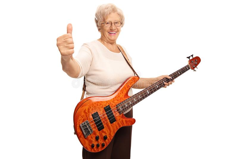 Happy senior woman with an electric guitar showing thumbs up. Isolated on white background stock photo