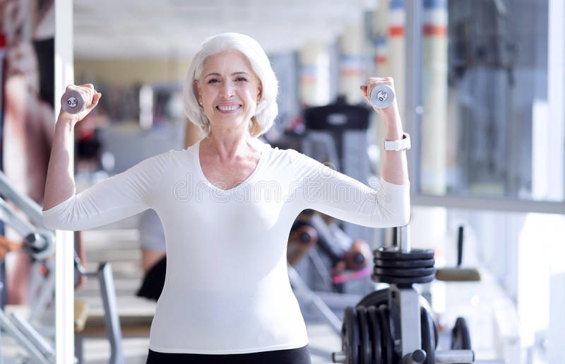 Happy senior woman exercising with dumbbells royalty free stock images