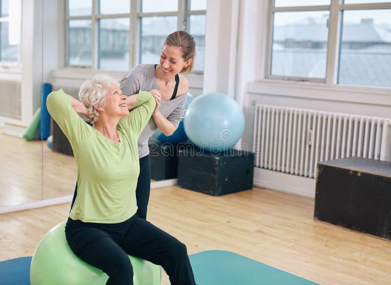 Happy senior woman exercising with female instructor stock image