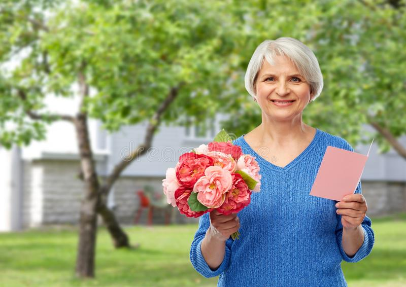 Happy senior woman with flowers and greeting card stock photo