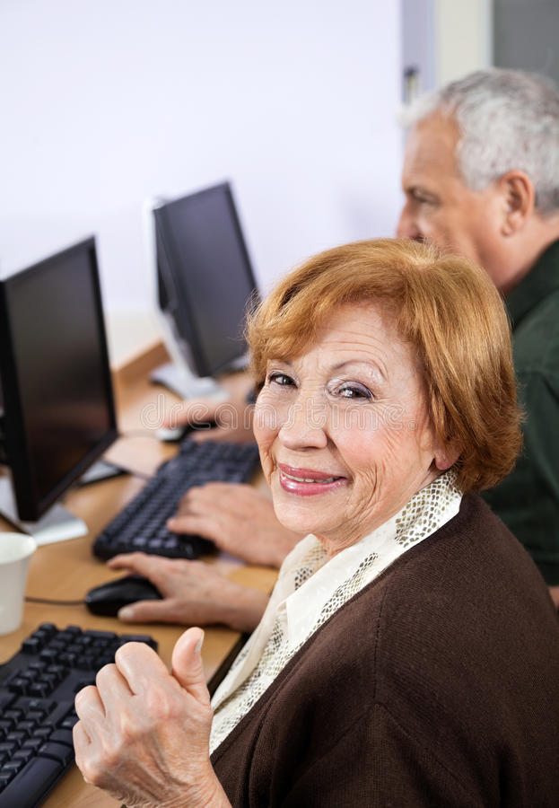 Happy Senior Woman Gesturing Thumbsup At Desk In Computer Class stock photos