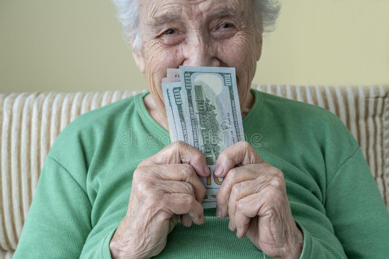 A happy senior woman holding american dollars royalty free stock photo