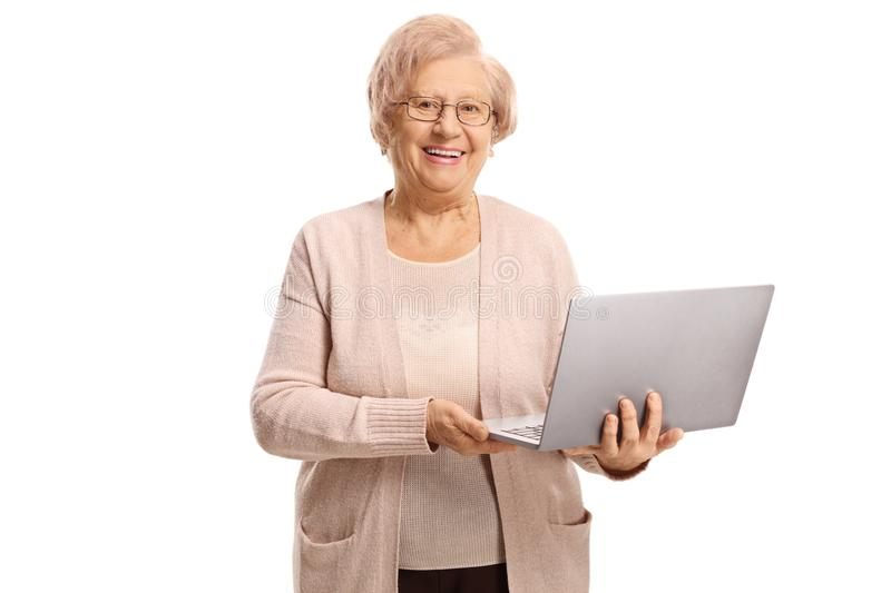 Happy senior woman holding a laptop computer stock image