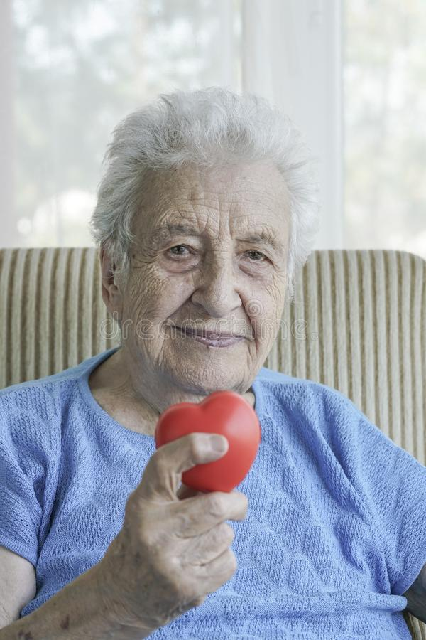Happy senior woman holding a red heart royalty free stock images