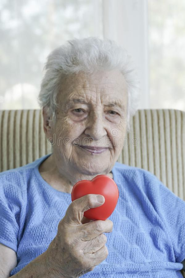 Happy senior woman holding a red heart stock images