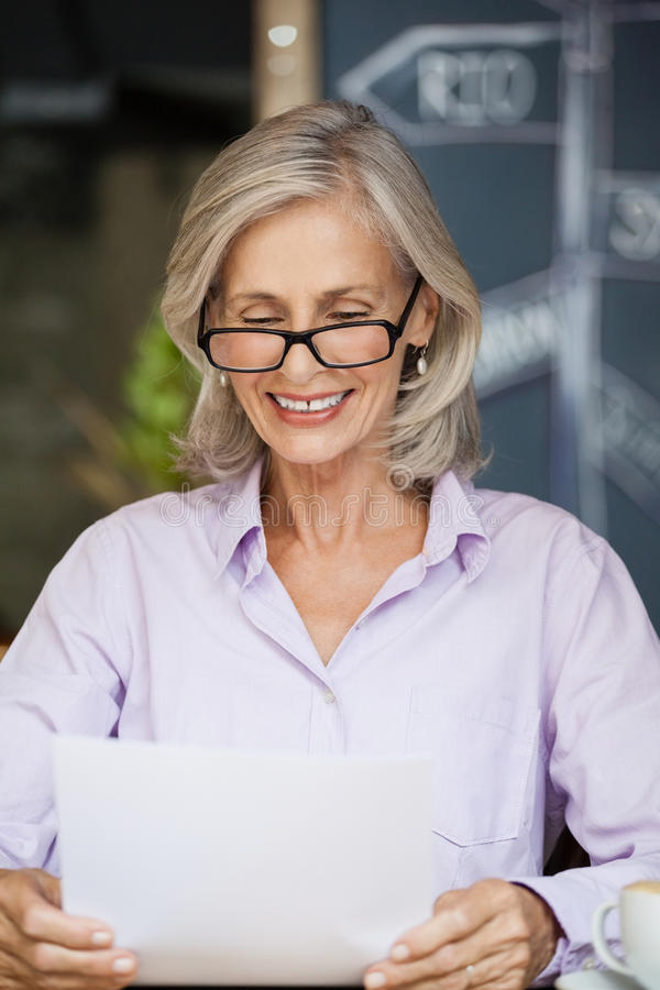Happy senior woman holding tablet computer stock photography