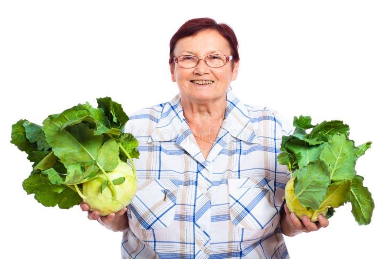 Happy senior woman with kohlrabi stock image