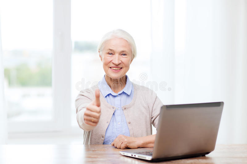 Happy senior woman with laptop showing thumbs up. Technology, age and people concept - happy senior woman with laptop computer at home showing thumbs up gesture stock photography