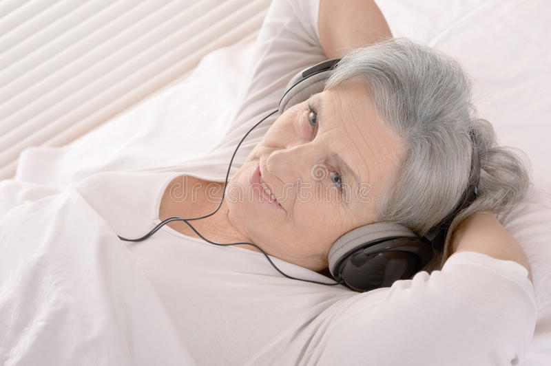 Happy senior woman listen a music in headphones resting in a bed royalty free stock photography