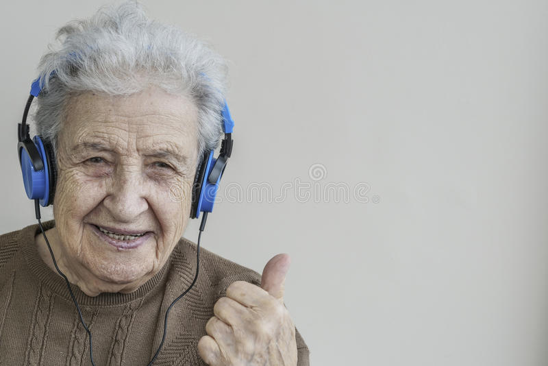 Happy senior woman listening music with headphones royalty free stock images
