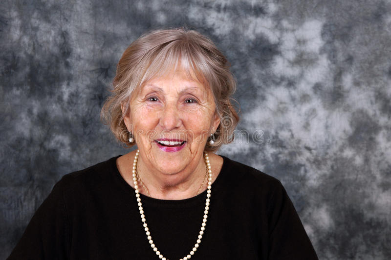 Happy senior woman with pearls stock photography