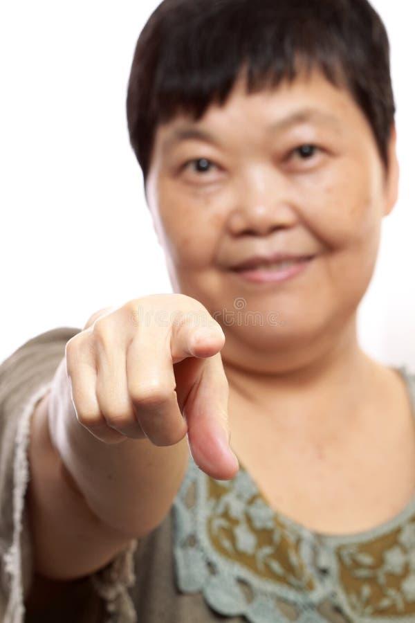 Happy senior woman pointing forwards on white. Portrait of a happy senior woman pointing forwards on white royalty free stock photos
