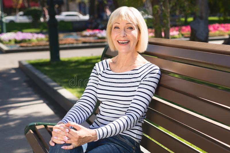 Happy senior woman relaxing on park bench stock photo