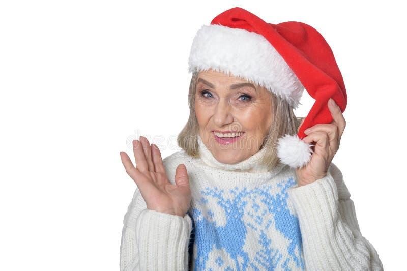Portrait of happy senior woman in Santa hat stock image