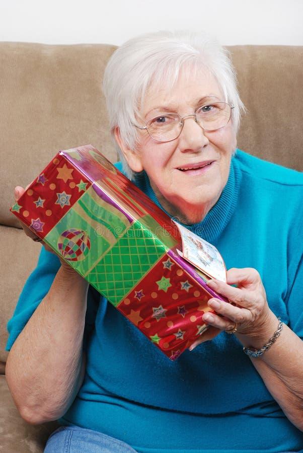 Happy Senior Woman Shaking Her Christmas Present Royalty Free Stock Photos
