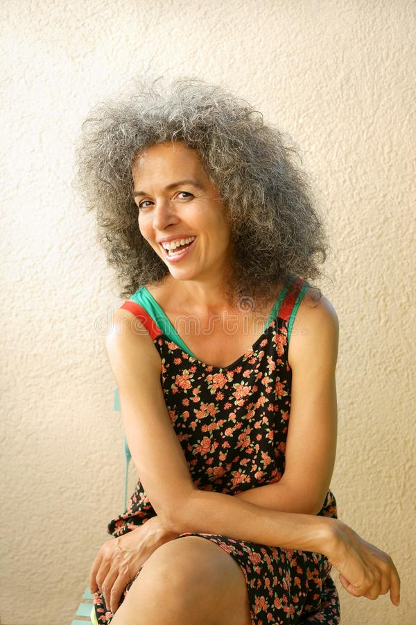 Smiling natural woman over 50 in summer dress. Happy senior woman sitting on a chair. Curly graying hair, latin type woman. Light wall background royalty free stock photos